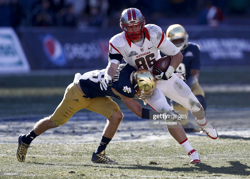 Austin Collinsworth #28 of the Notre Dame Fighting Irish tackles Tyler Kroft #86 of the Rutgers Scarlet Knights during the New Era Pinstripe Bowl between the Notre Dame Fighting Irish and the Rutgers Scarlet Knights at Yankee Stadium on December 28, 2013 in the Bronx borough of New York City.