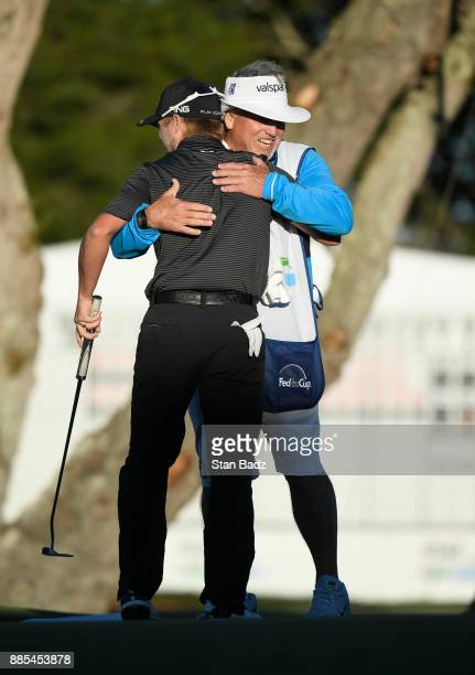 Austin Cook celebrates with his caddy on the 18th green during the final round of The RSM Classic at the Sea Island Resort Seaside Course on November...
