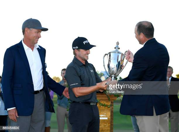 Austin Cook is presented the winners trophy on the 18th green after the final round of The RSM Classic at the Sea Island Resort Seaside Course on...