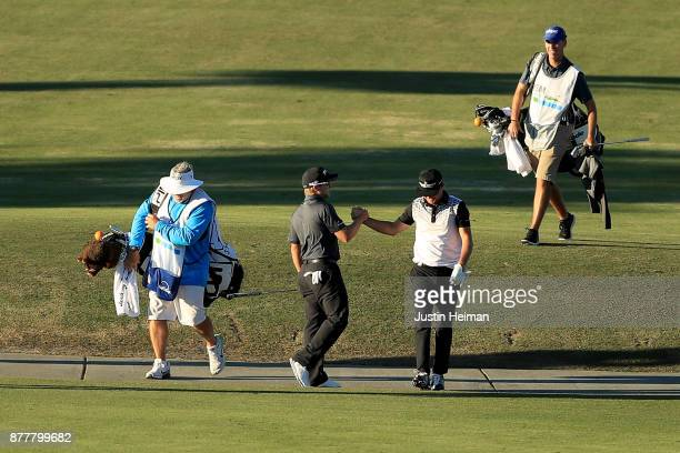 Austin Cook of United States congratulates Brian Gay of the United States after he holed out from 161 yards for eagle on the 18th hole during the...
