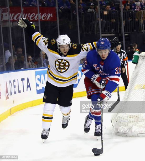 Austin Czarnik of the Boston Bruins holds his arms up to show the referee that he wasn't holding Jimmy Vesey of the New York Rangers during the first...