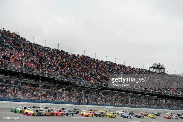 Austin Dillon driver of the AdvoCare Chevrolet and Travis Pastrana driver of the Roush Fenway Racing Ford lead the field at the start of the NASCAR...