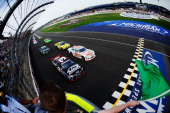 Austin Dillon driver of the AdvoCare Chevrolet leads Cole Whitt driver of the Clean Coal Chevrolet and the field to the green flag to start the...