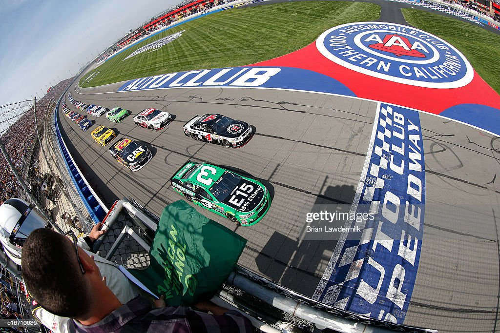 Austin Dillon driver of the American Ethanol Chevrolet and Kevin Harvick driver of the Jimmy John's Chevrolet lead a pack of cars at the start of the...