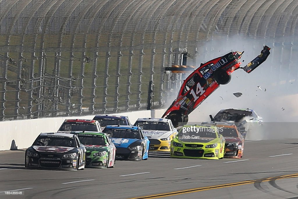 Austin Dillon, driver of the #14 Bass Pro Shops / Mobil 1 Chevrolet, and Casey Mears, driver of the #13 GEICO Ford, are involved in an incident during the NASCAR Sprint Cup Series Camping World RV Sales 500 at Talladega Superspeedway on October 20, 2013 in Talladega, Alabama.