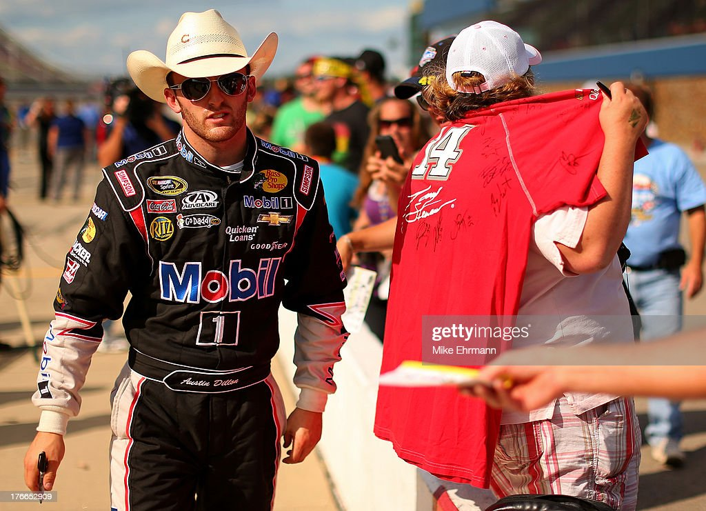 Austin Dillon, driver of the #14 Mobil 1 / Bass Pro Shops Chevrolet, signs autographs during qualifying for the NASCAR Sprint Cup Series 44th Annual Pure Michigan 400 at Michigan International Speedway on August 16, 2013 in Brooklyn, Michigan.