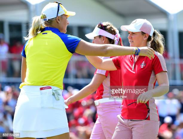 Austin Ernst of Team USA gets a hug from Anna Nordqvist of Team Europe after losing two up on the 17th hole during the morning foursomes matches of...