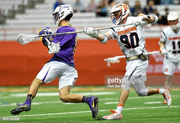 Austin Fusco of the Syracuse Orange checks the stick of Adam Osika of the Albany Great Danes during the fourth quarter at the Carrier Dome on...