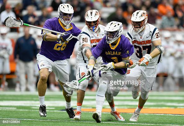 Austin Fusco of the Syracuse Orange checks the stick of TD Ierlan of the Albany Great Danes during the first quarter at the Carrier Dome on February...