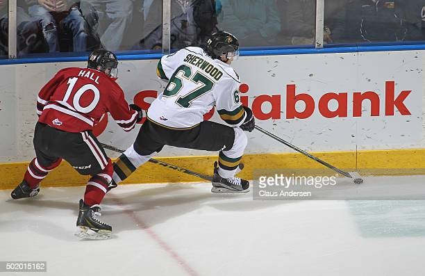 Austin Hall of the Guelph Storm skates to check Kole Sherwood of the London Knights during an OHL game at Budweiser Gardens on December 18 2015 in...