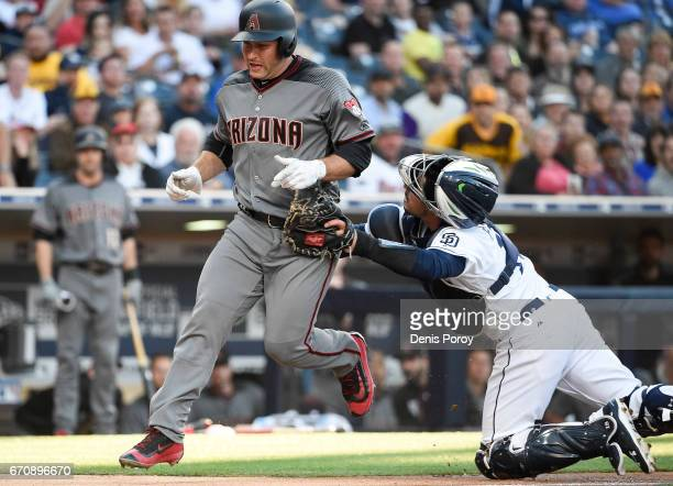 Austin Hedges of the San Diego Padres tags Chris Iannetta of the Arizona Diamondbacks at the plate during the second inning of a baseball game at...