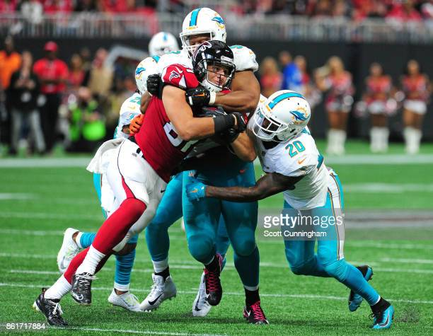 Austin Hooper of the Atlanta Falcons is tackled by Ndamukong Suh Reshad Jones and Damien Williams of the Miami Dolphins at MercedesBenz Stadium on...
