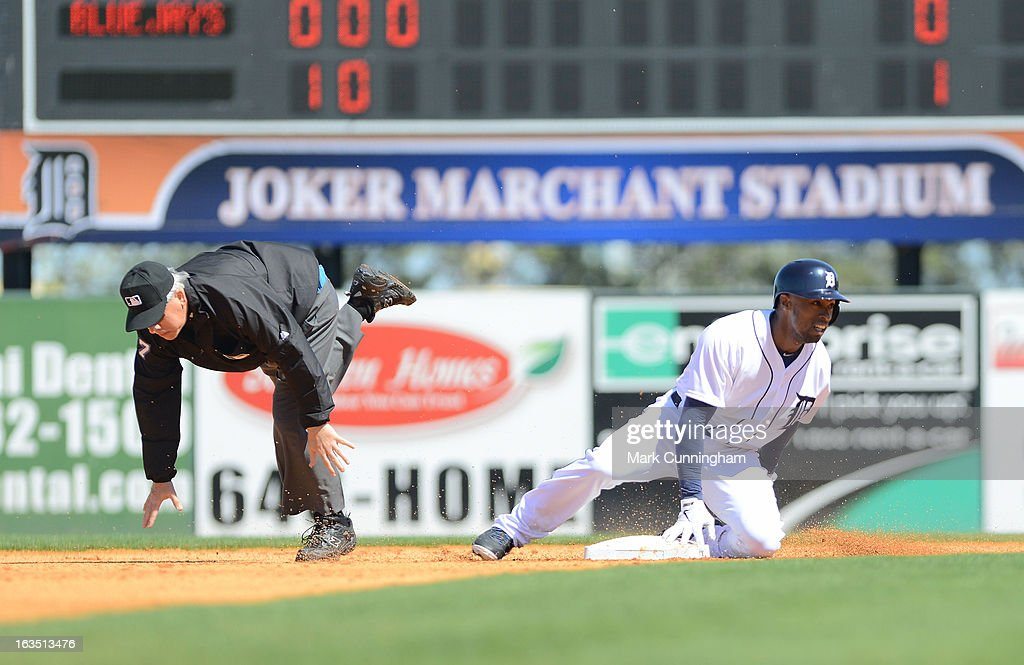 Austin Jackson #14 of the Detroit Tigers slides into second base umpire Larry Vanover and knocks him off his feet during the spring training game against the Toronto Blue Jays at Joker Marchant Stadium on March 6, 2013 in Lakeland, Florida. The Tigers defeated the Blue Jays 4-1.
