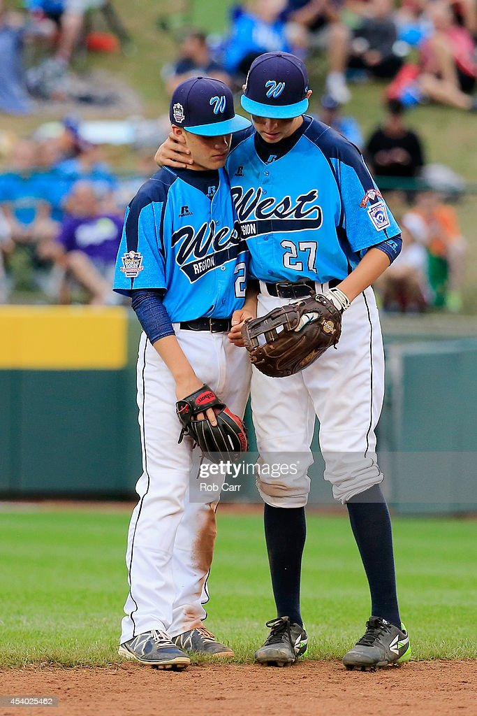Austin Kryszczuk #21 is consoled by Brennan Holligan #27 of the West Team from Las Vegas, Nevada after the Great Lakes Team from Chicago, Illinois scored a run during the fifth inning of the United States Championship game of the Little League World Series at Lamade Stadium on August 23, 2014 in South Williamsport, Pennsylvania.