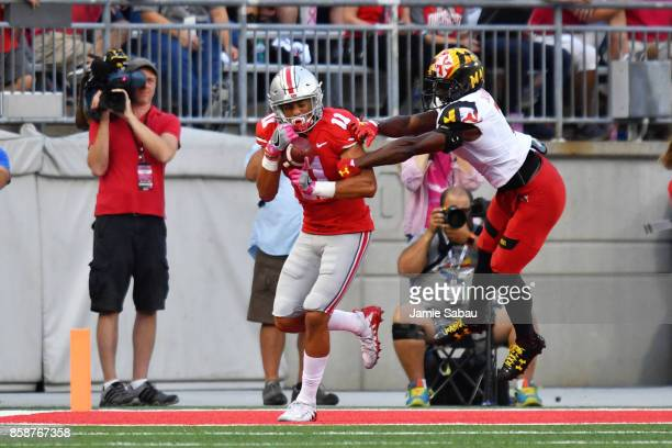 Austin Mack of the Ohio State Buckeyes makes 5yard touchdown reception in front of JC Jackson of the Maryland Terrapins at the end of the second...