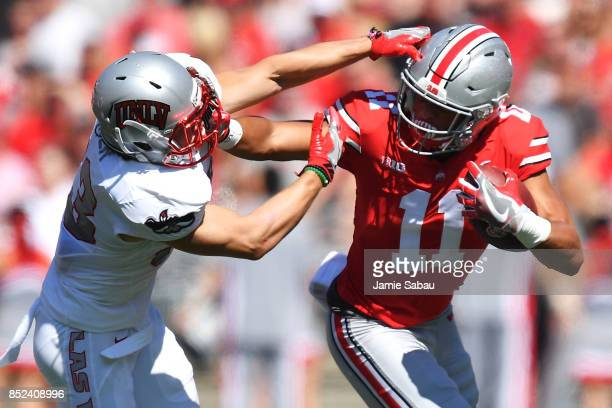 Austin Mack of the Ohio State Buckeyes stiff arms Dalton Baker of the UNLV Rebels in the first quarter after making a pass reception at Ohio Stadium...
