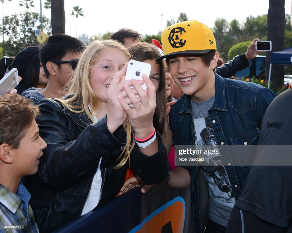 Austin Mahone takes pictures with fans at 'Extra' at Universal Studios Hollywood on December 6 2013 in Universal City California