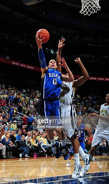 Austin Rivers of the Duke Blue Devils puts up a shot against Kammeon Holsey of the Georgia Tech Yellow Jackets at Philips Arena on January 7 2012 in...
