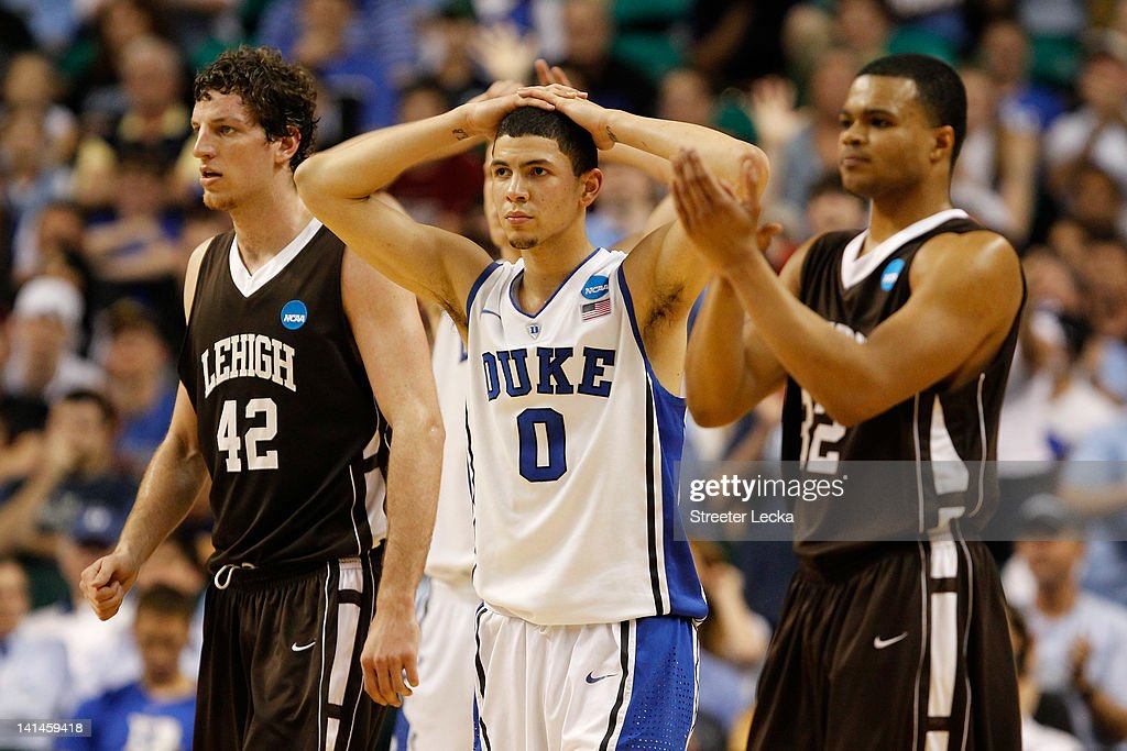 Austin Rivers of the Duke Blue Devils reacts as he stands between Gabe Knutson and BJ Bailey of the Lehigh Mountain Hawks in the second half during...