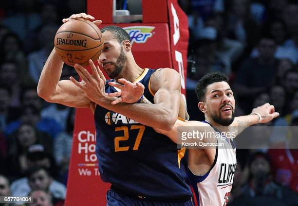 Austin Rivers of the Los Angeles Clippers reaches in and fouls Rudy Gobert of the Utah Jazz during the second half of the basketball game at Staples...