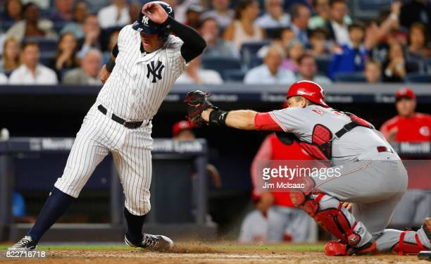 Austin Romine of the New York Yankees avoids a tag at home from Devin Mesoraco of the Cincinnati Reds during the fifth inning at Yankee Stadium on...