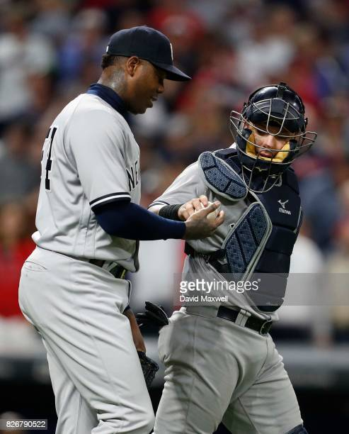 Austin Romine of the New York Yankees hands the ball to Aroldis Chapman after defeating the Cleveland Indians at Progressive Field on August 5 2017...