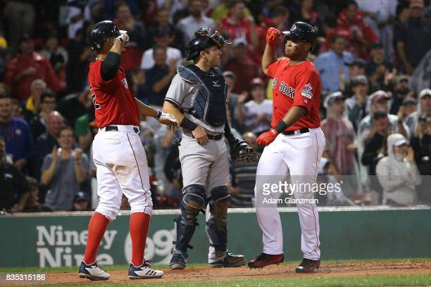 Austin Romine of the New York Yankees looks on as Rafael Devers high fives Xander Bogaerts of the Boston Red Sox after hitting a tworun home run in...