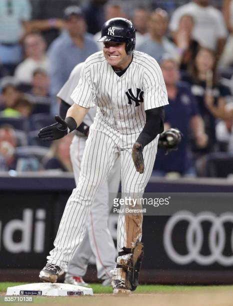 Austin Romine of the New York Yankees reactsnby clapping his hands at third base after hitting a triple in an MLB baseball game against the Boston...