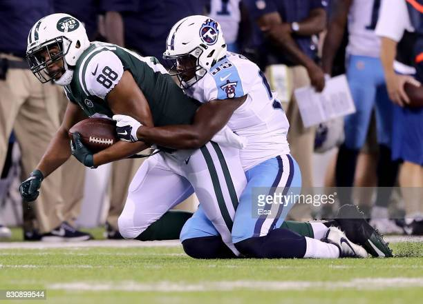Austin SeferianJenkins of the New York Jets is tackled by Jayon Brown of the Tennessee Titans in the second quarter during a preseason game at...