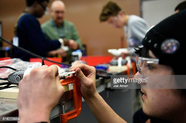 Austin Stout 18 shaping a part while building a flywheel car using 3D printed components during a technician class at Emily Griffith Technical...
