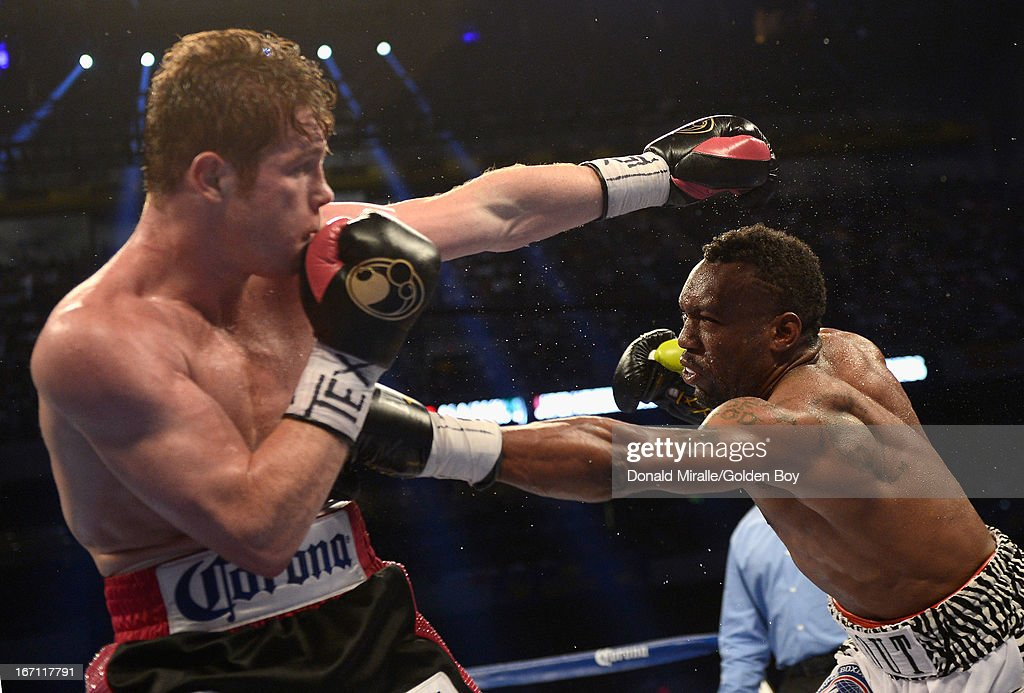 Austin Trout punches Canelo Alvarez (L) of Mexico en route to Alvarez's unanimous 12-round decision over Trout during the WBC, WBA, and Vacant Ring Magazine Super Welterweight Title at Alamodome on April 20, 2013 in San Antonio, Texas.