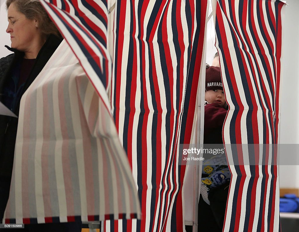 Austin Varney, 15 mths old, peeks out of the voting booth curtain as his mother Alexandria Varney votes in a polling station setup in the First Baptist Church on February 9, 2016 in Nashua, New Hampshire. Voters throughout the state are heading to the polls as the New Hampshire Primary, also known as the first-in-the-nation primary, continues the process of selecting the next president of the United States.