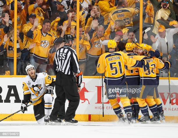 Austin Watson Craig Smith Matt Irwin of the Nashville Predators celebrate a goal while Carter Rowney of the Pittsburgh Penguins kneels on the ice...