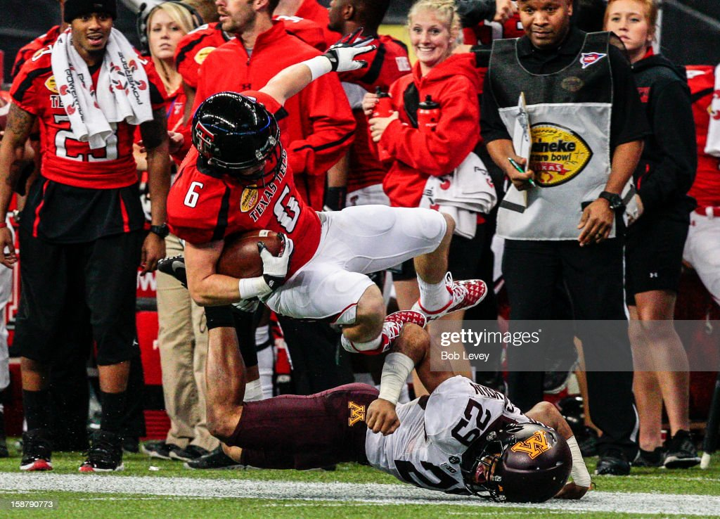 Austin Zouzalik #6 of the Texas Tech Red Raiders is knocked out of bounds by Briean Boddy-Calhoun #29 of the Minnesota Golden Gophers during the Meineke Car Care of Texas Bowl at Reliant Stadium on December 28, 2012 in Houston, Texas. Texas Tech defeated Minnesota 34-31.