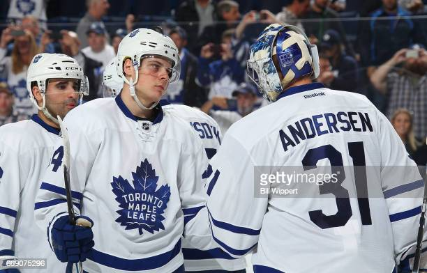 Auston Matthews and Frederik Andersen of the Toronto Maple Leafs celebrate a victory against the Buffalo Sabres during an NHL game at the KeyBank...