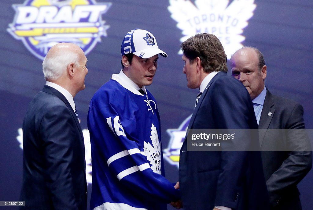 <a gi-track='captionPersonalityLinkClicked' href=/galleries/search?phrase=Auston+Matthews&family=editorial&specificpeople=13452736 ng-click='$event.stopPropagation()'>Auston Matthews</a> celebrates onstage with Toronto Maple Leafs General Manager <a gi-track='captionPersonalityLinkClicked' href=/galleries/search?phrase=Lou+Lamoriello&family=editorial&specificpeople=540467 ng-click='$event.stopPropagation()'>Lou Lamoriello</a> and <a gi-track='captionPersonalityLinkClicked' href=/galleries/search?phrase=Mike+Babcock&family=editorial&specificpeople=226668 ng-click='$event.stopPropagation()'>Mike Babcock</a> after being selected first overall during round one of the 2016 NHL Draft on June 24, 2016 in Buffalo, New York.