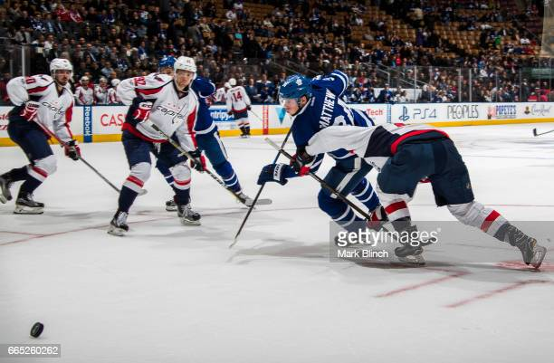 Auston Matthews of the Toronto Maple Leafs battles against Evgeny Kuznetsov of the Washington Capitals during the third period at the Air Canada...