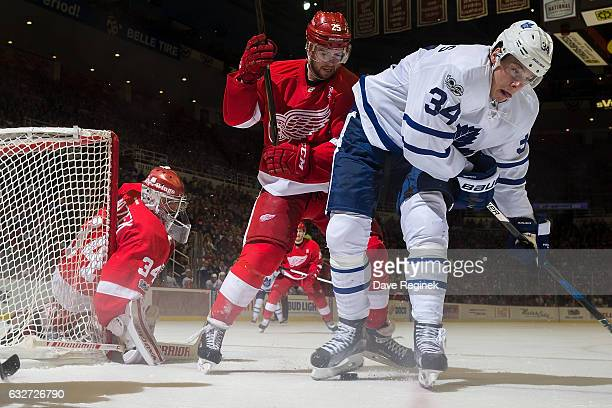 Auston Matthews of the Toronto Maple Leafs battles for the puck with Mike Green of the Detroit Red Wings in front of goaltender Petr Mrazek of the...