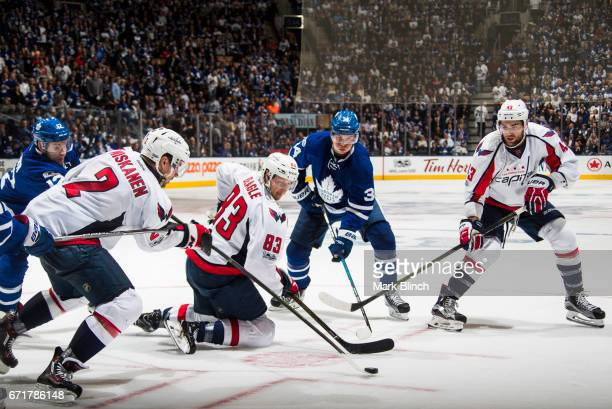 Auston Matthews of the Toronto Maple Leafs battles for the puck with Matt Niskanen Jay Beagle and Tom Wilson of the Washington Capitals during the...