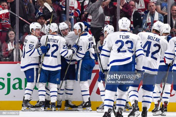 Auston Matthews of the Toronto Maple Leafs celebrates his overtime goal with teammates against the Montreal Canadiens during the NHL game at the Bell...