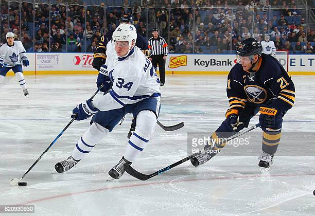 Auston Matthews of the Toronto Maple Leafs controls the puck against Kyle Okposo of the Buffalo Sabres during an NHL game at the KeyBank Center on...