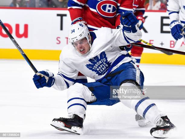 Auston Matthews of the Toronto Maple Leafs falls as he scores his first period goal against the Montreal Canadiens during the NHL game at the Bell...