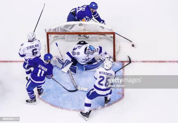 Auston Matthews of the Toronto Maple Leafs goes around the net with teammate Zach Hyman against Andrei Vasilevskiy Luke Witkowski and Anton Stralman...