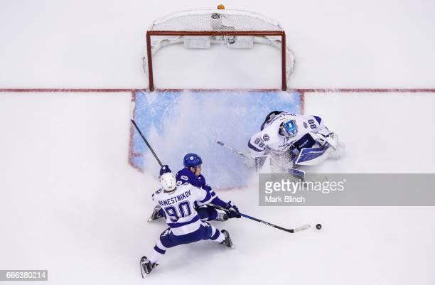 Auston Matthews of the Toronto Maple Leafs goes to the net against Andrei Vasilevskiy and Vladislav Namestnikov of the Tampa Bay Lightning during the...