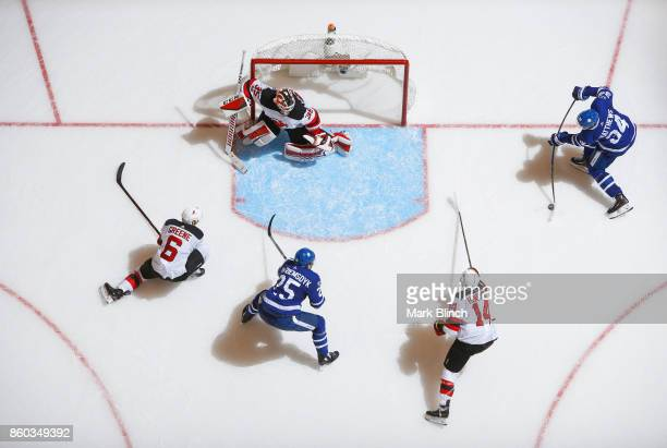 Auston Matthews of the Toronto Maple Leafs shoots to score on Cory Schneider of the New Jersey Devils as his teammates Andy Greene and Adam Henrique...