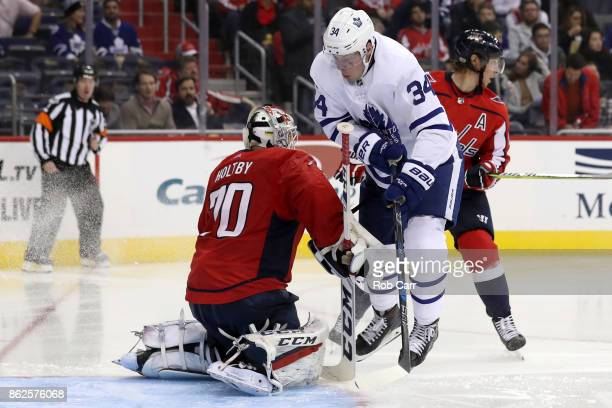 Auston Matthews of the Toronto Maple Leafs skates into goalie Braden Holtby of the Washington Capitals in the third period at Capital One Arena on...