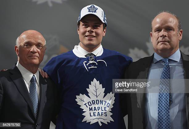 Auston Matthews poses onstage with general manager Lou Lamoriello left and director of player personnel Mark Hunter of the Toronto Maple Leafs after...