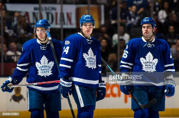 Auston Matthews Roman Polak and Zach Hyman of the Toronto Maple Leafs stand on the ice in a break in play agains the Boston Bruins during the third...