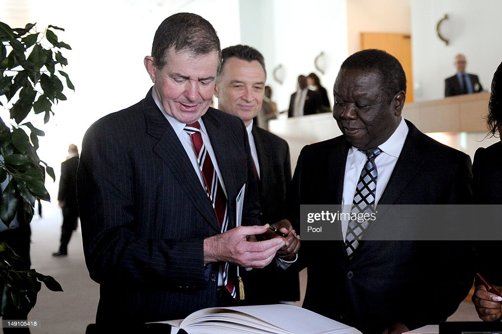 Austraian House of Representatives Seaker Peter Slipper invites the Prime Minister of Zimbabwe <a gi-track='captionPersonalityLinkClicked' href=/galleries/search?phrase=Morgan+Tsvangirai&family=editorial&specificpeople=800701 ng-click='$event.stopPropagation()'>Morgan Tsvangirai</a> to sign the Parliament House visitors book during a lunch on July 23, 2012 in Canberra, Australia. Australia is the third largest donor to Zimbabwe with assistance focused on water, sanitation and economic growth.
