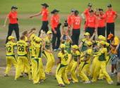 Australia celebrate after winning the Final as England look on during the ICC Women's World Twenty20 Bangladesh 2014 between Australia Women and...